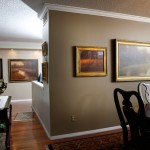 A trio of Brent Cotton landscapes in the dining room of Bullards Denver condominium, with the million-dollar wall in the background.